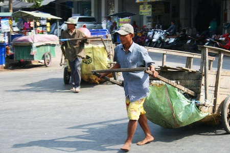 third wheel: POI PET, THAILAND - JANUARY 19: Man pulls a cart along the road on January 19, 2011 in Poi Pet, Thailand.