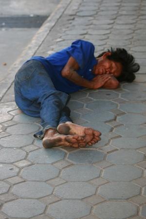 BANGKOK - el 5 de enero: Thai hombre duerme por el lado de la carretera el 5 de enero de 2010 en Bangkok, Tailandia.