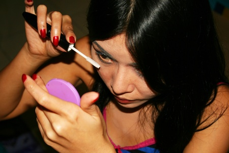 Asian woman applying makeup. photo