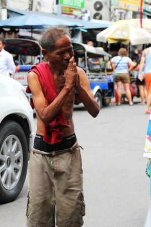 Thai man begs for money on Khaosarn road in Bangkok, Thailand.
