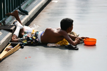 BANGKOK - JANUARI 10: Thaise kreupele man smeekt om geld op een brug op 10 januari 2010 in Bangkok, Thailand.