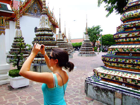 Woman taking a photo in Wat Pho, Bangkok, Thailand  photo