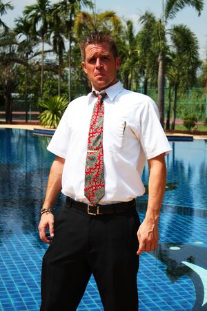 Man outside a swimming pool in Thailand  photo