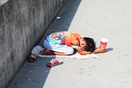 BANGKOK - JULY 24  Thai child begs beside motorway in Rangsit on 24 July, 2012 in Bangkok, Thailand
