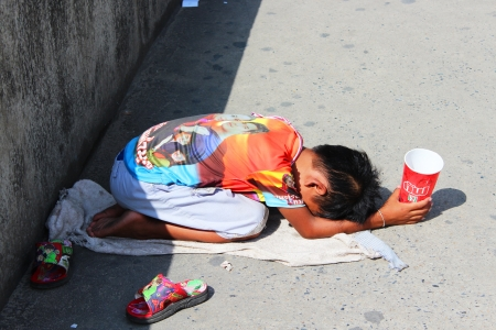 BANGKOK - JULY 24  Thai child begs beside motorway in Rangsit on 24 July, 2012 in Bangkok, Thailand