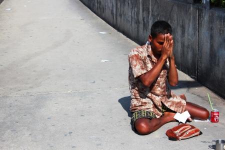 BANGKOK - JULY 24  Thai man begs beside motorway