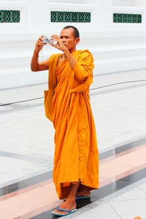 BANGKOK - AUGUST 20  Thai Buddhist monk taking a photograph inside temple grounds on August 20, 2012 in Bangkok, Thailand