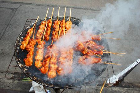 Chicken cooking on a grill in Thailand  photo