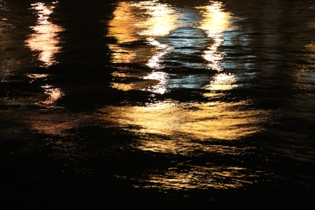 irridescent: Golden Reflections on River at Night, England