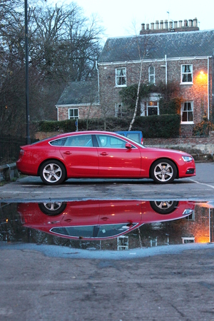 Sporty Red Car Reflected in Puddle, England