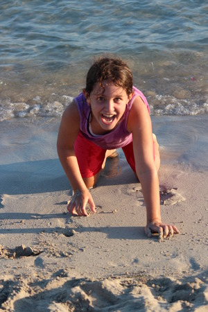 Girl Playing With Sand On Beach, Cyprus. Stock Photo