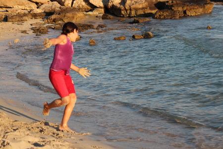 frizz: Girl Throwing Sand on Beach, Cyprus.