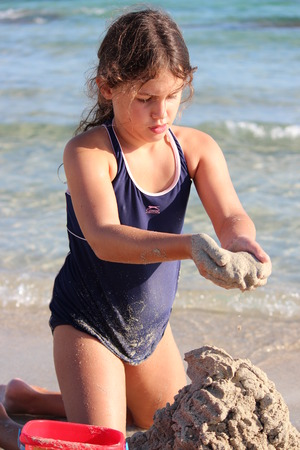 swimming costumes: Girl Building Sandcastles on Beach, Cyprus.