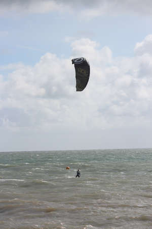 wetsuit: Man In Wetsuit Paragliding, England, September 2015.