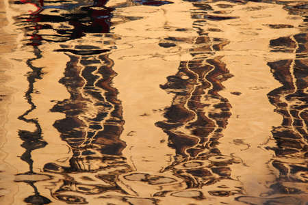 irridescent: Gold, Brown and Beige Ripples on Water at Sunset.