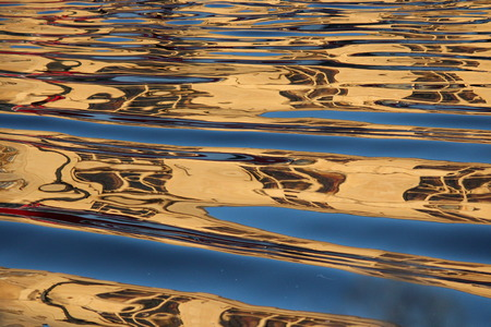 irridescent: Gold and Blue Ripples on Water at Sunset.