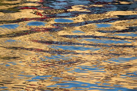irridescent: Gold and Blue Ripples Reflecting off Water at Sunset.