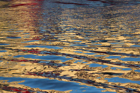 irridescent: Gold and Blue Reflections on Water at Sunset.