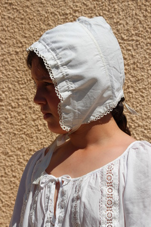 wisps: Young Girl Wearing Victorian Cotton Bonnet. Stock Photo