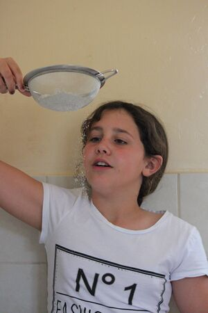 frizz: Young Girl Playing With Flour and Sieve in Kitchen.