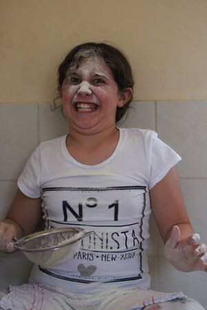 sieve: Young Girl Playing With Flour and Sieve in Kitchen.