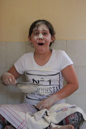wisps: Young Girl Playing With Flour and Sieve in Kitchen.