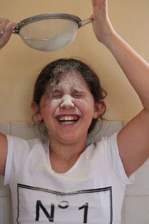 frizz: Young Girl Playing With flour and Sieve in Kitchen. Stock Photo