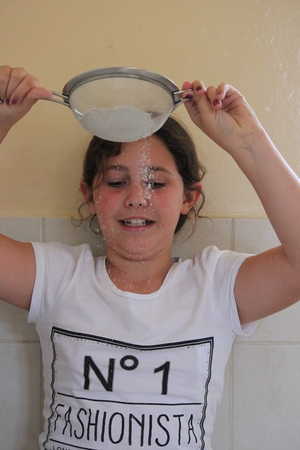 sift: Young Girl Playing With flour and Sieve in Kitchen. Stock Photo