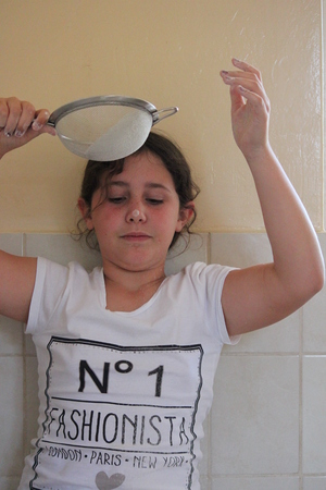 sieve: Young Girl Playing With flour and Sieve in Kitchen. Stock Photo