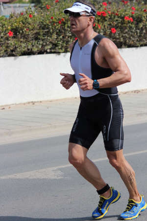 lycra: Editorial: Runner Completing Final Stage of Ayia Napa Triathlon, Nissi Beach, Cyprus; Sunday 3rd April 2016.