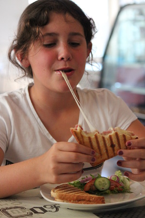 animate: Young Girl Eating Cheese Toastie in Little Cafe, Cyprus.