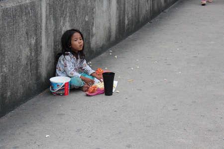 subsistence: Editorial: Young Girl Begging on Concrete Walkway Over Motorway Interchange, Rangsit, Pathumthani, North Bangkok, 19th October 2013. Editorial