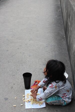 Editorial: Young Girl Begging on Concrete Walkway Over Motorway Interchange, Rangsit, Pathumthani, North Bangkok, 19th October 2013. Editorial