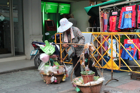laden: Editorial: Old Woman Carries Baskets of Produce to Sell on Kao San Road, Central Bangkok, on 13th October 2013. Editorial