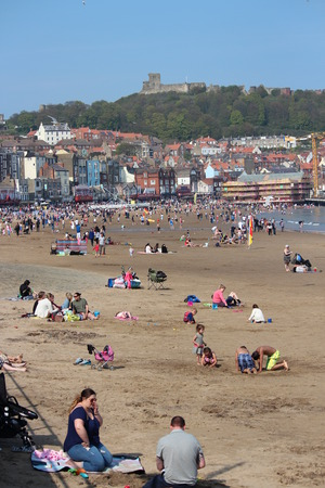 hottest: Editorial: Crowds of British Holidaymakers Flock to the Seaside and Choose Scarborough Beach on the Hottest Day of the Year; Sunday 8th May 2016. Editorial