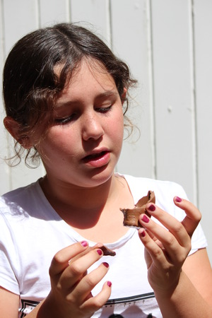 wisps: Young Girl Eating Chocolate Easter Gift in Bright Sunshine.