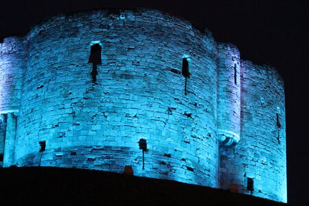 turreted: Blue Floodlit Norman Stone Tower.