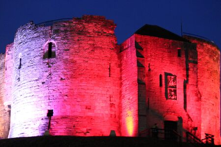turreted: Red Floodlit Norman Stone Tower. Stock Photo