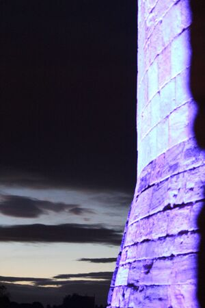 turreted: Purple Floodlit Medieval Stone Wall With Evening Sky. Stock Photo