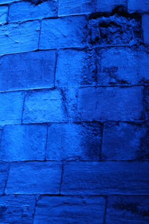 turreted: Blue Floodlit Medieval Stone Wall. Stock Photo