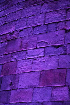 turreted: Purple Floodlit Medieval Stone Wall. Stock Photo