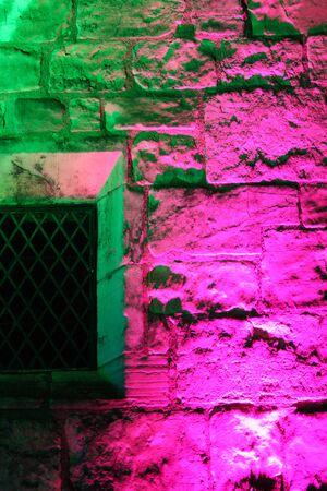 Rainbow Floodlighting on Medieval Stone Building. Stock Photo