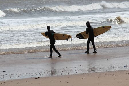 Surfers Brave the Waves on A Cold, Grey, Winters Day in April.