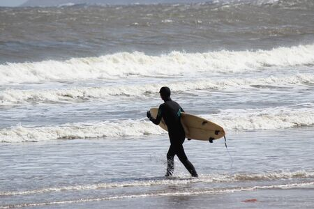 silver surfer: Surfers Brave the Waves on A Cold, Grey, Winters Day in April.
