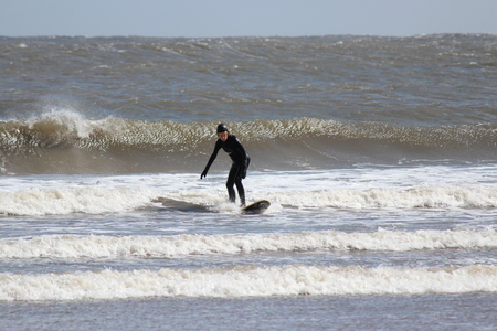 currents: Surfers Brave the Waves on A Cold, Grey, Winters Day in April.