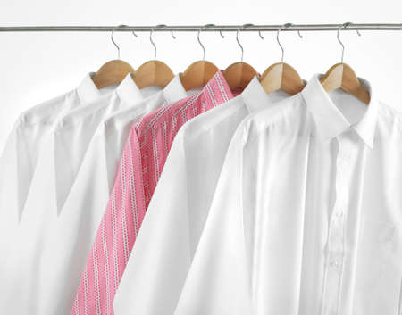 Odd one out. A row of shirts hanging. Stock Photo