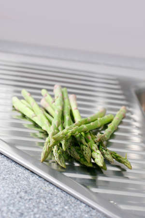 washed: Washed asparagus on a stainless steal kitchen draining board.