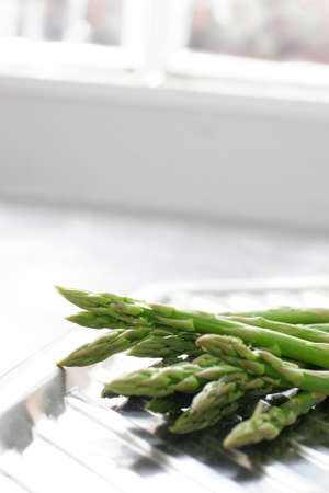 draining: Washed asparagus on a stainless steal kitchen draining board.