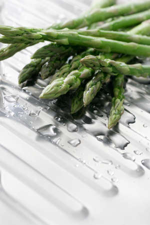 stainless steal: Washed asparagus on a stainless steal kitchen draining board.