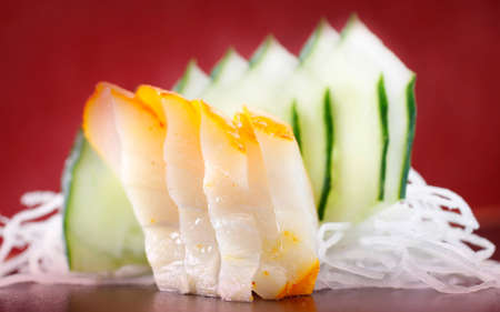 haddock: Haddock sushimi sushi dish with cucumber on a red background Stock Photo